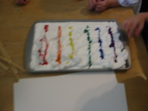 Marble painting step 1: Shaving cream on a baking pan with a tempera rainbow.